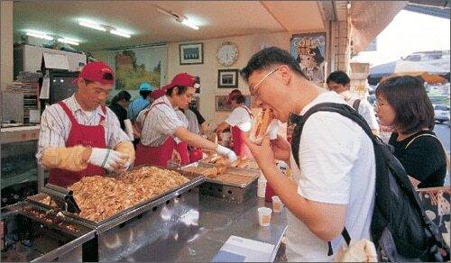 지난 2004년 고려대 앞 '영철 스트리트 버거'에서 일하는 이영철씨. 2000년 리어카 노점으로 시작해 당시엔 작은 매장을 운영했다. /조선일보 DB