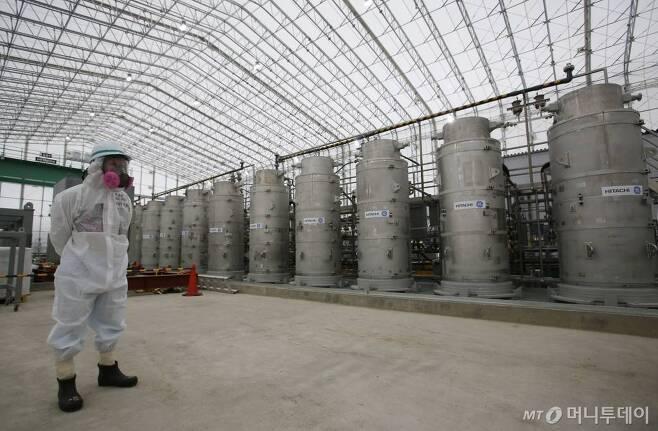 [오쿠마=AP/뉴시스] 일본 후쿠시마현 오쿠마에 있는 원전 오염수 처리시설에서 2014년 11월 12일 한 직원이 방사성 물질 보호복을 입고 서있다. 2019.12. 29