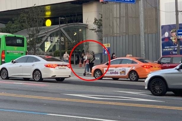 23일 오후 5시 37분 홍대입구역 4번 출구 인근 도로에서 남녀 두 명이 공유 전동킥보드를 같이 타고 있다. (사진=박서빈 기자)