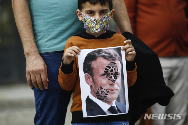 """[이스탄불=AP/뉴시스]25일(현지시간) 터키 이스탄불에서 한 어린이가 프랑스에 대한 항의 시위 도중 신발 자국이 찍힌 에마뉘엘 마크롱 프랑스 대통령의 사진을 들고 있다. 레제프 타이이프 에르도안 터키 대통령은 마크롱 대통령에 대해 연이틀 """"정신과 검사를 받을 필요가 있다""""라며 비난했다. . 앞서 프랑스는 에르도안의 정신 감정이 필요하다는 말에 항의의 표시로 터키 주재 자국 대사를 소환했다. 2020.10.26."""