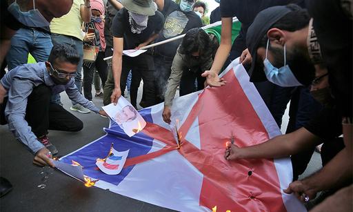 26일(현지시간) 이라크 수도 바그다드에서 반(反) 프랑스 시위대가 프랑스 국기와 에마뉘엘 마크롱 프랑스 대통령 얼굴 사진을 불태우고 있다. 바그다드=AP연합뉴스