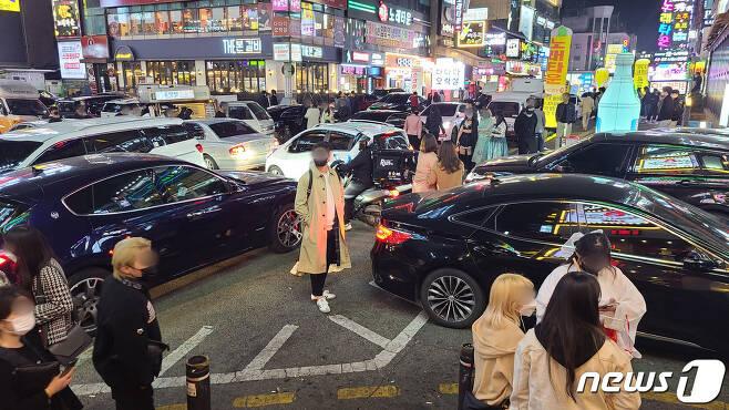 핼러윈데이를 하루 앞둔 30일 밤 경기 수원시 인계동 무비사거리 일대. 차량과 인파가 뒤섞여 혼잡을 이루고 있다. © 뉴스1