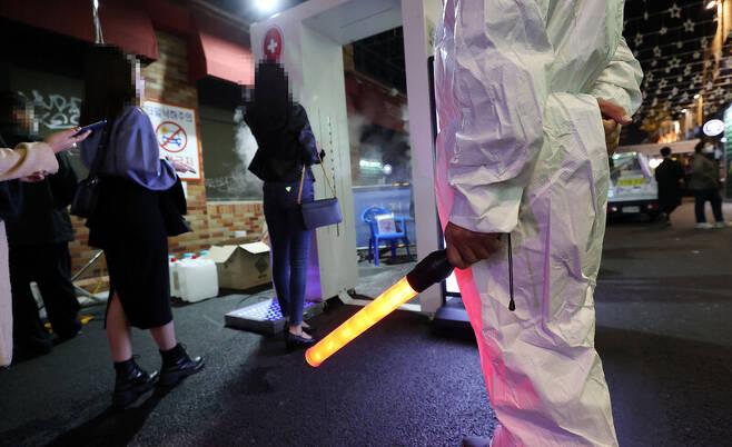 핼러윈데이를 하루 앞둔 30일 오후 서울 용산구 이태원 거리 입구에 설치된 코로나19 방역 게이트를 시민들이 통과하고 있다. 연합뉴스