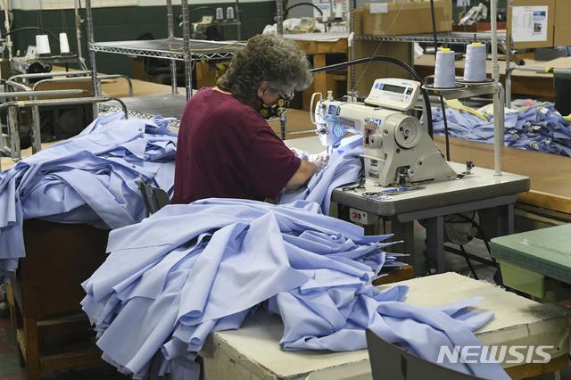 [애실랜드(미 펜실베이니아주)=AP/뉴시스]지난 10월20일 미 펜실베이니아주 애실랜드의 한 공장에서 여성 노동자 1명이 우체국 직원들의 셔츠 바느질 작업을 하고 있다. 미 공급관리협회(ISM)은 2일(현지시간) 지난달 미국의 제조업 지수가 59.3으로 9월의 55.4에서 3.9포인트 상승하며 2년여만에 최고를 기록했다고 밝혔다. 2020.11.3