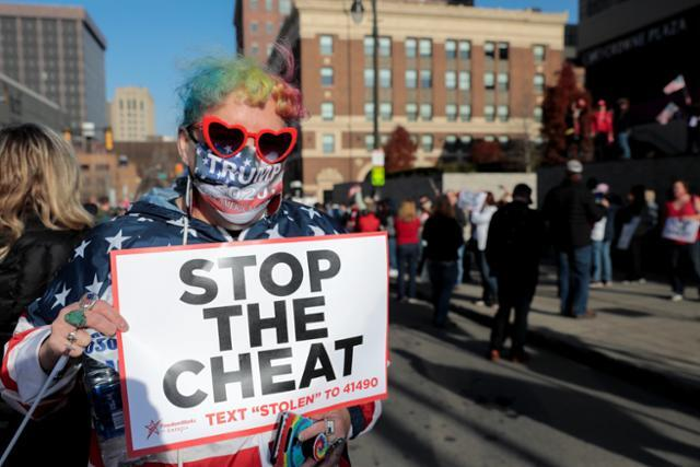 미국 미시간주 디트로이트의 TCF센터에 마련된 개표장 밖에서 6일(현지시간) 도널드 트럼프 대통령 지지자들이 '속임수를 중단하라'는 팻말을 들고 시위를 벌이고 있다. 디트로이트=로이터 연합뉴스