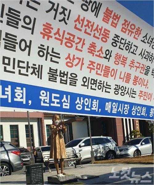 광양 평화의 소녀상 앞에 소녀상 이전을 요구하는 인근 상인들의 현수막이 걸려있다.(사진=최창민 기자)