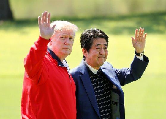 도널드 트럼프 미국 대통령과 아베 신조 전 일본 총리가 2019년 5월 26일 일본 지바현의 모바라 컨트리 클럽에서 만난 뒤 기자들에게 손을 들어 인사하고 있다. [로이터=연합뉴스]