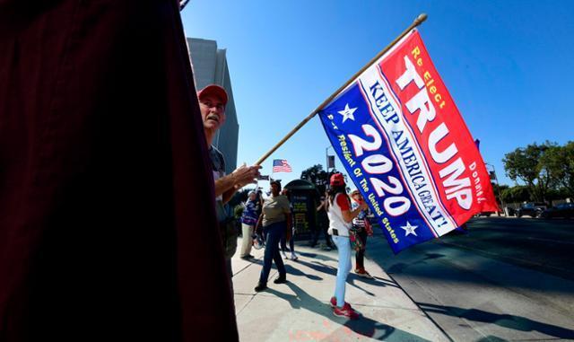 도널드 트럼프 미국 대통령 지지자들이 지난 11일 캘리포니아주 로스앤젤레스의 한 거리에서 트럼프를 응원하는 의미의 깃발을 들고 서 있다. 로스앤젤레스=AFP 연합뉴스