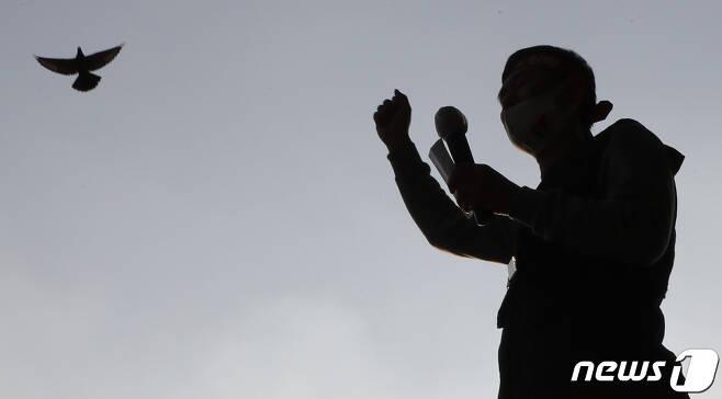 """13일 서울 청계천 평화시장 앞에서 열린 '전태일 열사 50주기 """"인간답게 살고 싶다!"""" 11.13 전태일들의 행진'에서 비정규직 이제그만 공동투쟁 관계자들이 청와대로 행진하는 가운데 비둘기 한마리가 날아오르고 있다. 2020.11.13/뉴스1 © News1 이성철 기자"""