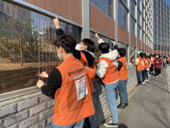 경기도및 하남시 자원봉사센터 소속 자원봉사자들이 14일 오후 하남시 미사중학교 일대 투명 방음벽 구간에서 방음벽 개선작업을 벌이고 있다.  경기도자원봉사센터 제공