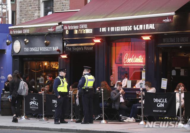 [더블린=AP/뉴시스]21일(현지시간) 아일랜드 더블린의 한 술집 밖에 마스크를 쓰지 않은 사람들이 앉아 있다. 코로나19가 급증하면서 미홀 마틴 아일랜드 총리는 오는 22일부터 6주간 코로나19 대응 조치를 5단계로 격상한다고 밝혔다. 이에 따라 비필수업종 상점은 폐쇄되고 식당은 포장 영업만 허용되며 시민들은 집에서 반경 5km 이내에 머물러야 한다. 2020.10.22.