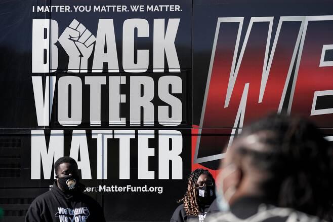 '흑인의 표는 중요하다' 캠페인 지지자들이 미 대선일인 지난 3일 노스캐롤라이나주의 그레이엄 시빅 센터에 마련된 투표소 앞에서 투표를 독려하고 있다./AP 연합뉴스