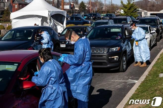 미국 오하이오주 콜럼버스 소재 한 드라이브스루 진료소에서 의료진이 코로나19 검사를 시행 중이다. © AFP=뉴스1