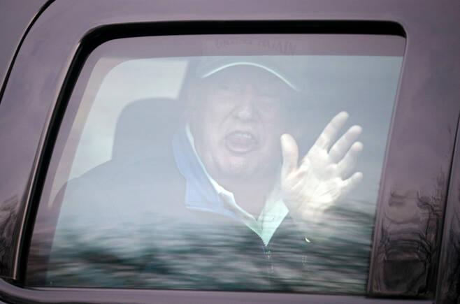 도널드 트럼프 미국 대통령이 22일(현지시간) 버지니아주에 위치한 트럼프 내셔널 골프 클럽으로 이동하는 차량 안에서 지지자를 향해 손을 흔들고 있다. [로이터]