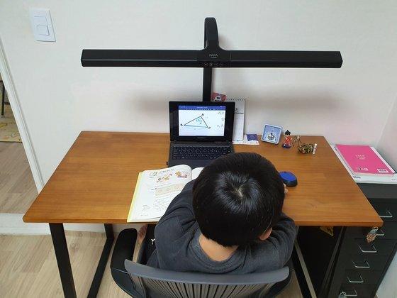 집에서 온라인 수업을 듣는 중학교 1학년 학생. 이 학생은 ″온라인 수업은 15분이면 끝난다″며 ″친구들은 다 2배속으로 수업을 듣는다″고 말했다. 사진 위문희 기자