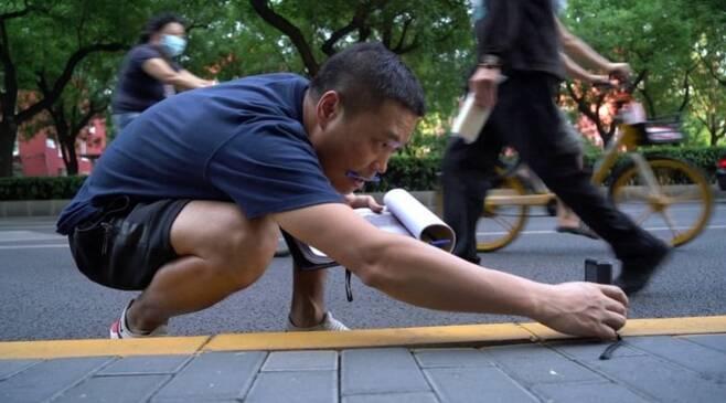 중국 베이징 도로의 길이를 측정하고 있는 작가 덩 유펑. /BBC