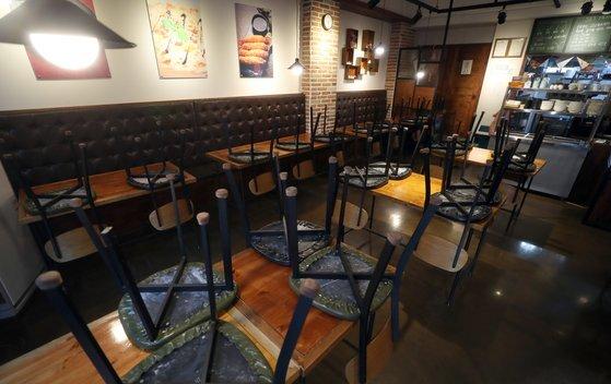 사회적 거리 두기 2단계가 시행중인 22일 경남 하동군 하동읍 한 식당 테이블 위로 의자가 놓여 있다.   식당 관계자는 코로나19 확산으로 이날 영업을 중단하고 내일부터 사회적 거리두기에 맞춰 영업할 예정이라고 말했다. 연합뉴스