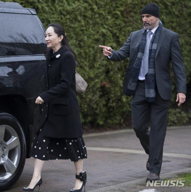 [밴쿠버=AP/뉴시스]20일(현지시간) 캐나다 밴쿠버에서 멍완저우 화웨이 부회장(왼쪽)이 미국 인도 재판 참석을 위해 자택을 나서고 있다. 왼쪽 발목에 위치추적 전자장치가 노출돼 있다. 2020.01.21.