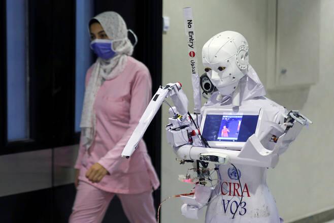 지난 18일(현지시간) 이집트 북부 탄타의 한 병원에서 간호사 로봇 시라-03이 한 간호사 앞을 지나며 체온 측정을 하는 모습. (사진=로이터 연합뉴스)