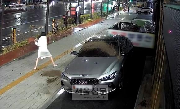 지난 19일 새벽 1시 40분쯤 한 여성이 서울 송파구 석촌역 3번 출구 인근 건물 앞에 주차된 제네시스 차량에 화분을 던지고 있다. [사진=독자제공]