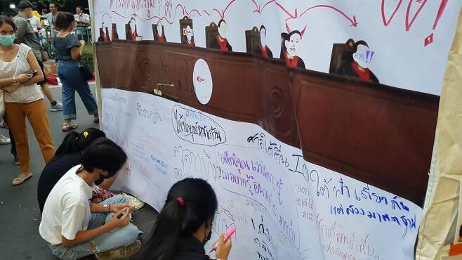 헌재 재판관들을 묘사한 대형 현수막에 비판 글을 적는 시위대. [방콕=김남권 특파원]