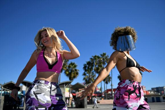 코로나19 확산을 막기 위한 자택 대피령이 내려지기 하루 전인 29일(현지시간) 미국 캘리포니아주 로스앤젤레스의 해변에서 사람들이 롤러블레이드를 타며 여유를 즐기고 있다.로이터 연합뉴스