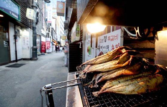 수도권의 사회적 거리두기 2단계가 유지되는 가운데 지난달 30일 점심시간 서울 중구 서울시청 인근 생선구이 식당 앞에 생선이 쌓여 있다.