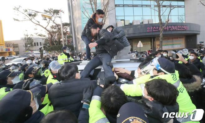 12일 오전 안산시내에서 일부 시민들이 거주지로 향하는 조두순이 탑승한 차량을 막아서고 있다. 2020.12.12/뉴스1 © News1 조태형 기자