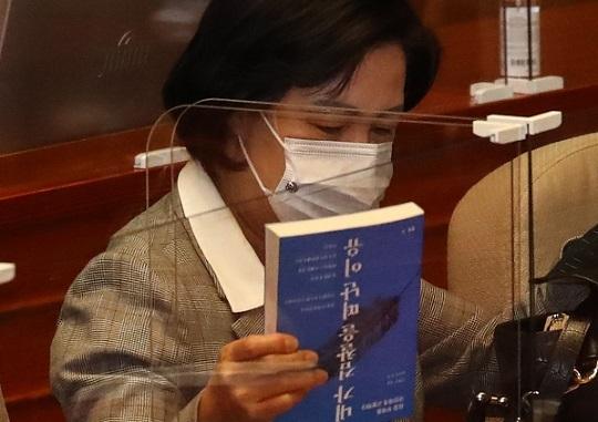 지난 9일 국회 본회의를 앞두고 본회의장 장관석에 앉아 '내가 검찰을 떠난 이유'라는 책을 가방에서 꺼내고 있는 추미애 법무부장관. 연합뉴스