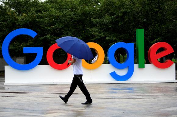 미국 50개 주 가운데 절반이 넘는 주 사법당국이 구글에 대해 반독점 위반 혐의로 조사할 예정이다. 사진은 지난 2018년  8월 27일 중국 상하이에서 우산을 쓴 한 시민이 '구글 광고'판 앞을 지나고 있다. 상하이 이 로이터 연합뉴스