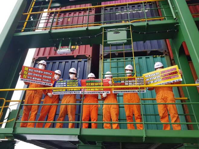 HMM 컨테이너선에 승선 중인 항해사와 기관사들이 피켓을 들고 사측에 처우 개선을 요구하고 있다. (사진=HMM 해원연합노동조합)