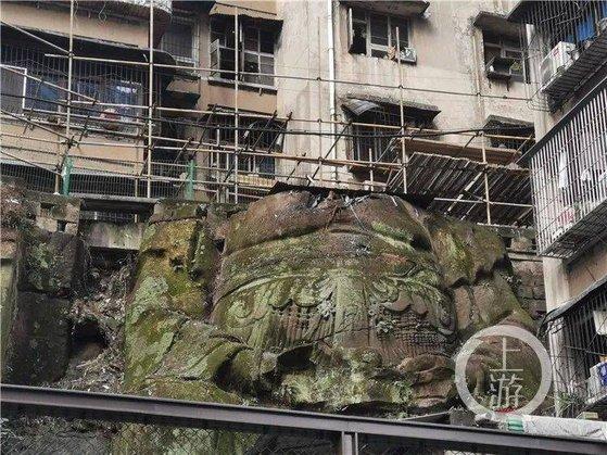 중국 충칭의 한 주택 단지에서 아파트를 떠받치고 있는 머리 없는 대형 석각이 발견돼 커다란 화제가 되고 있다. 불상이냐 아니냐는 논쟁도 뜨겁다. [중국 남방도시보망 캡처]