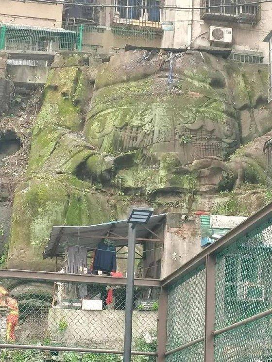 중국 충칭의 아파트 단지에서 발견된 대형 석각은 머리가 훼손됐으나 두 손과 배, 옷깃 등의 모습은 생생하게 남아있다. [중국 남방도시보망 캡처]