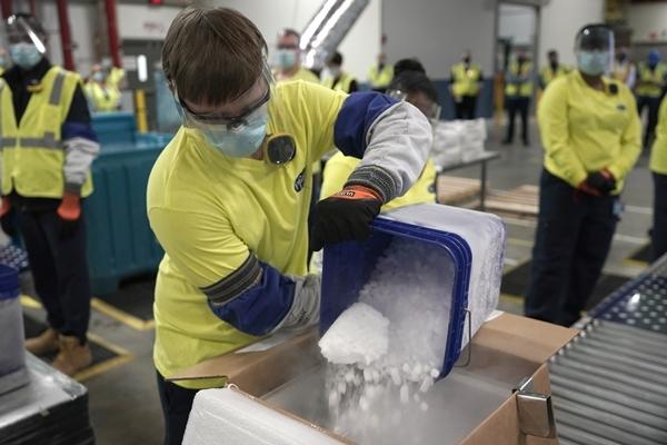 미국 미시간주 포티지의 화이자 제약공장에서 지난 13일(현지시간) 직원들이 코로나19 백신 운반용 특수상자에 드라이아이스를 넣고 있다. AP 연합뉴스