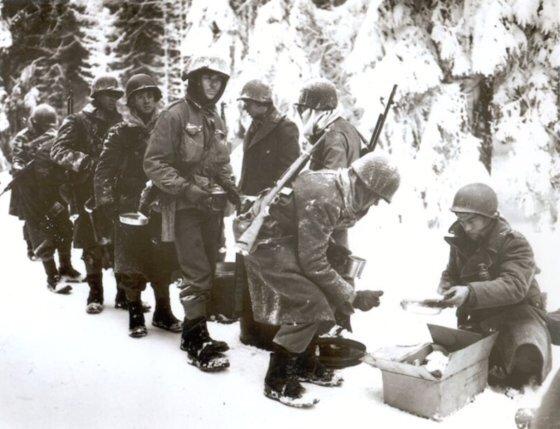 1944년 12월 16일 독일군 기습으로 시작된 벌지전투는 이듬해1월 27일까지 이어졌다. 기습을 받아 고립돼 참호전을 치룬 미군이 식사 배급을 받고 있다. [사진 미 육군]