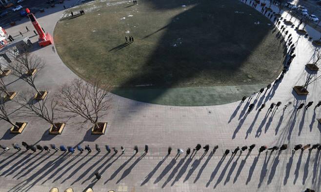 17일 서울 중구 서울광장에 마련된 신종 코로나바이러스 감염증(코로나19) 임시 선별진료소에서 시민들이 검사를 받기 위해 줄을 서 있다. 연합뉴스