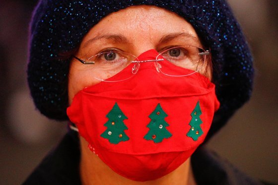 지난 23일 이탈리아의 로마에서 한 여성이 성탄 축하 무늬가 새겨진 마스크를 착용하고 있다. 이탈리아도 이번 성탄절을 이동 제한 속에서 보낼 전망이다. 로이터=연합뉴스