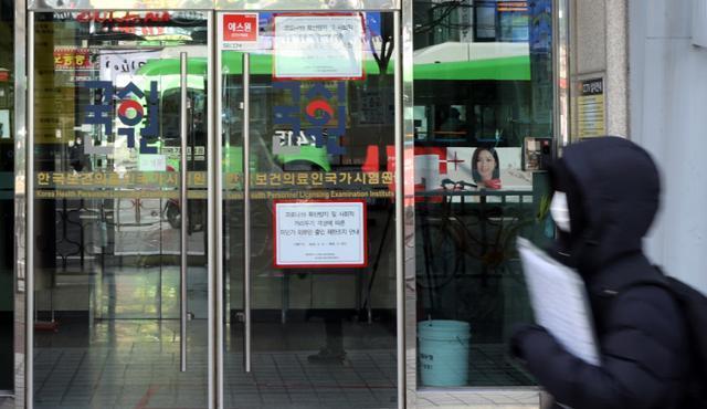 정부가 내년 하반기로 예정된 의사 국가고시 실기시험을 상·하반기로 나눠 2차례로 치르기로 했다고 발표한 31일 서울 광진구 한국보건의료인국가시험원 앞을 한 시민이 지나가고 있다. 연합뉴스