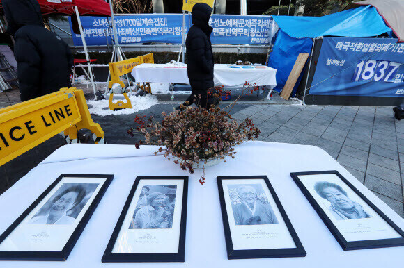 Photos of former comfort women in front of the Statue of Peace in Seoul. (Yonhap News)