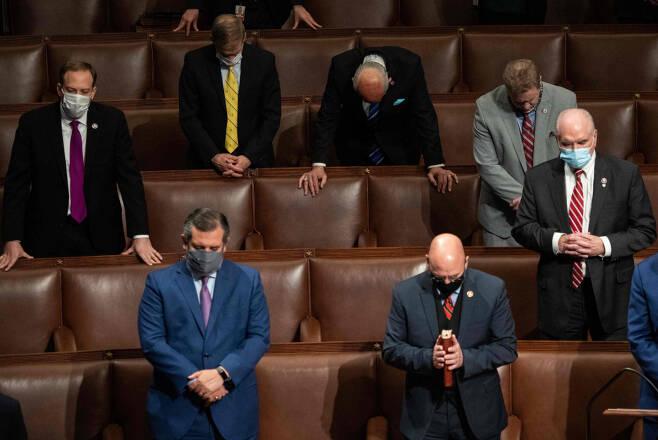 미 공화당 소속 의원들이 1월7일(현지 시각) 선거인단 투표를 처리하기 위해 재소집된 상·하원 합동회의에서 마이크 펜스 부통령이 조 바이든 후보의 당선을 최종 인증하자 기도를 올리고 있다. ⓒ AFP 연합