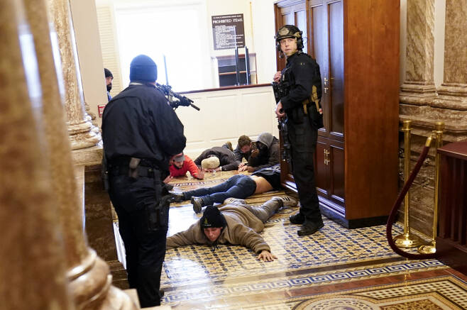 미 의회 경찰이 1월6일(현지 시각) 워싱턴DC 연방 의사당 내 하원 본회의장에 침입한 시위대를 엎드리게 한 후 총을 겨누고 있다. ⓒ AP 연합