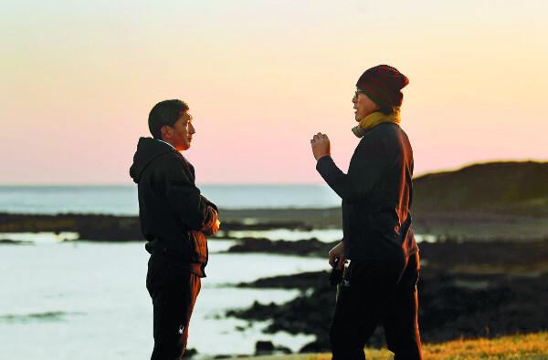 이명욱(왼쪽)씨와 도현욱씨가 석양이 지는 서귀포 해안에서 대화하고 있다.