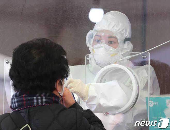 13일 서울역 광장에 마련된 임시선별진료소에서 의료진이 검체 채취를 하고 있다. 2021.1.13/뉴스1 © News1 이성철 기자
