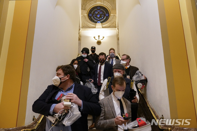 [워싱턴=AP/뉴시스]6일(현지시간) 미  의사당에 난입한 도널드 트럼프 대통령 지지자들이 하원에 침입하려하자 안에 있던 의원들이 대피하고 있다. 2021.01.07.