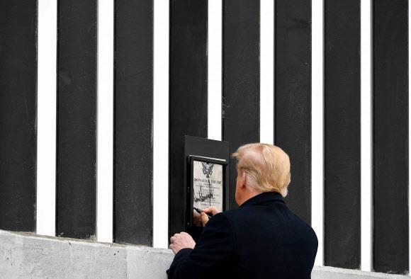 도널드 트럼프 미국 대통령이 12일(현지시간) 텍사스주 알라모의 미국·멕시코 국경장벽을 시찰하던 중 장벽에 부착된 명판에 서명을 하고 있다.알라모 AFP 연합뉴스