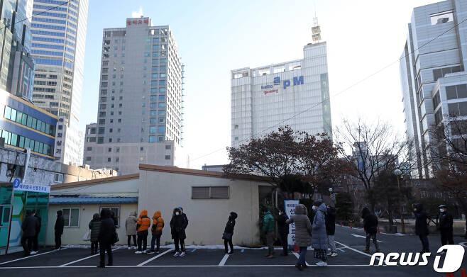 17일 오전 서울 중구 국립중앙의료원에 마련된 신종 코로나바이러스 감염증(코로나19) 해외 출국 선별진료소에서 시민들이 검사를 받기 위해 길게 줄을 늘어서 있다.  2021.1.17/뉴스1 © News1 오대일 기자
