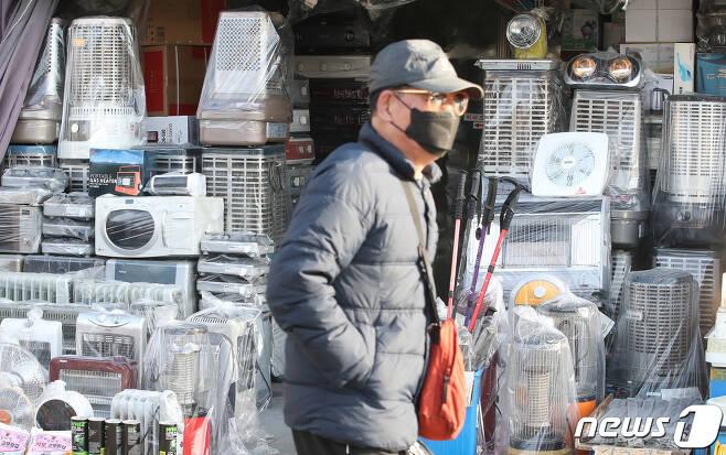 17일 오후 서울 중구 황학동 중앙시장을 찾은 한 시민이 진열된 난방기기 앞을 지나고 있다. 2021.1.17/뉴스1 © News1 임세영 기자