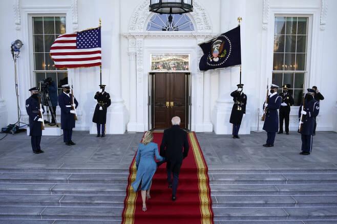 조 바이든 미국 대통령이 20일(현지시간) 부인 질 바이든 여사와 함께 백악관의 북측 현관인 노스 포티코에 도착해 계단을 오르고 있다. AP 연합뉴스