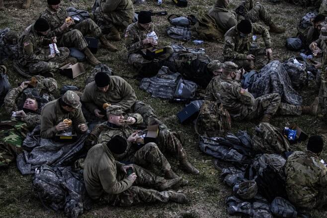 미국 아이다호 주 방위군이 21일 아침 워싱턴 DC 연방의사당 동편 잔디밭에서 취침후 기상해 간편식으로 아침 식사를 하고 있다. EPA=연합뉴스