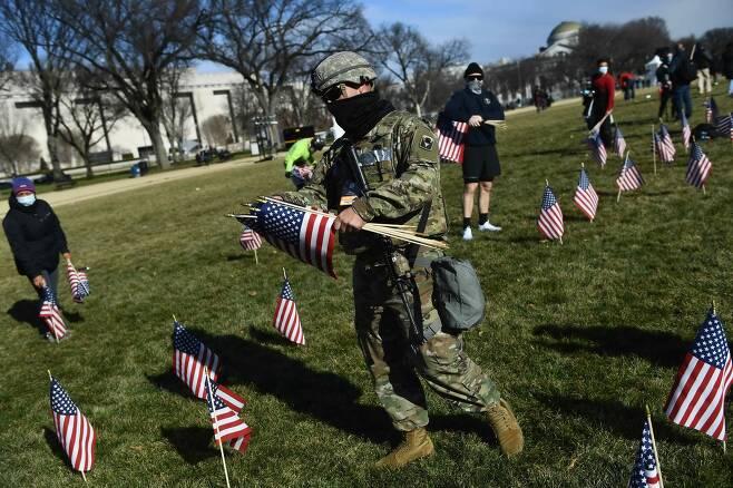 한 주 방위군 병사가 워싱턴 DC의 내셔널 몰에서 국기를 모으고 있다. 대통령 취임식 때 축하 인파가 몰리는 내서널 몰은 이번 취임식에서는 20만 개의 국기로 장식됐다. AFP=연합뉴스
